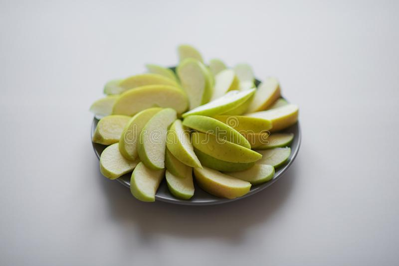 Slices of green apple laid out on a gray plate in a circle on a gray background. Vegetarian snack, healthy snack, food stock photo