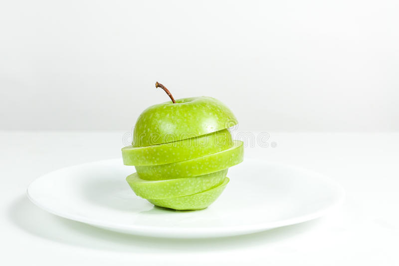 Slices of green apple in a plate. Slices of green apple in a white plate stock image