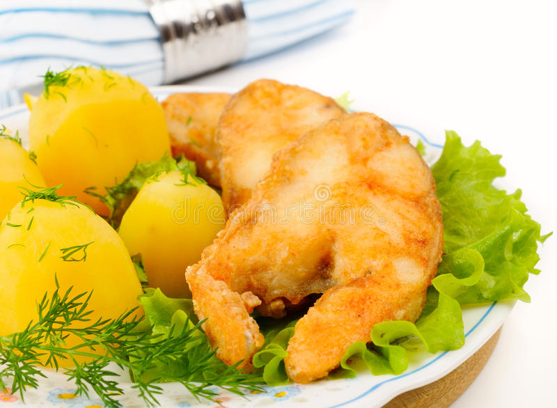 Slices of grilled sea bass. With boiled potatoes royalty free stock image