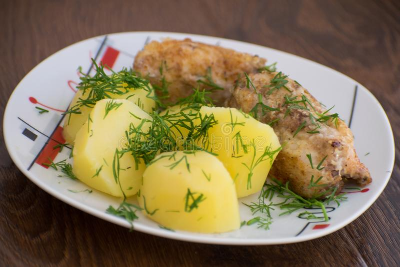 Slices of grilled sea bass with boiled potatoes on the plate. Slices of grilled sea bass with boiled potatoes stock image