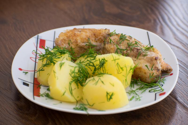 Slices of grilled sea bass with boiled potatoes on the plate. Slices of grilled sea bass with boiled potatoes stock photography