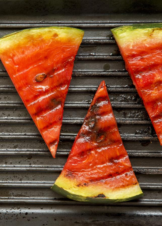 Slices of grilled watermelon in grilling pan, top view. Healthy summer fruit. Close-up royalty free stock photography
