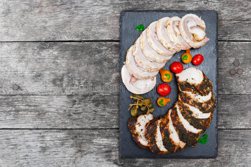 Slices of Homemade meatloaf, veal and pork tenderloin stuffed with vegetables on black slate stone chalkboard on wooden background royalty free stock photography
