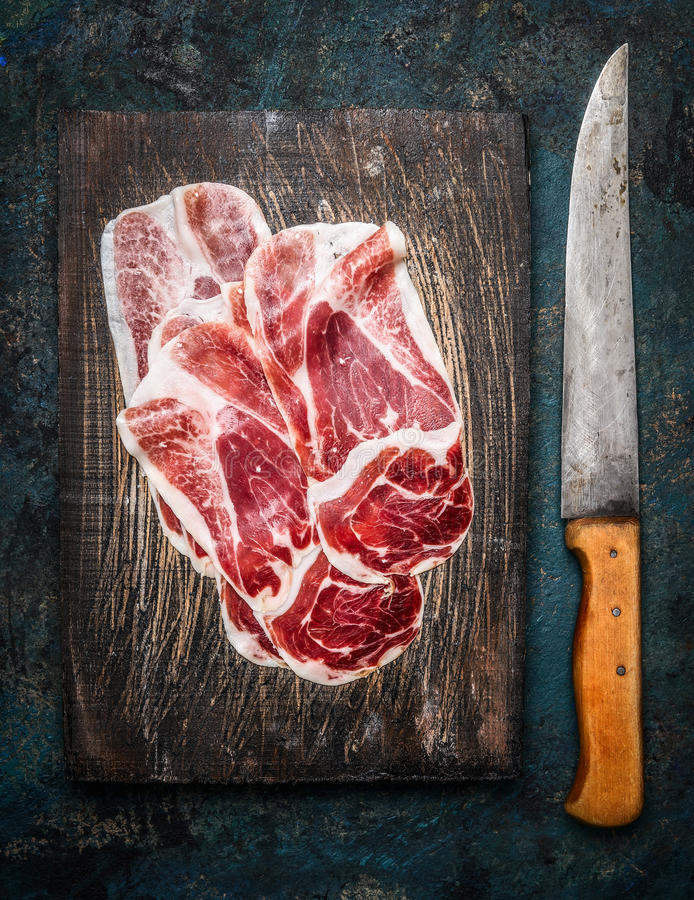 Slices of Iberico ham Cebo with kitchen knife on rustic wooden background. Top view stock photos
