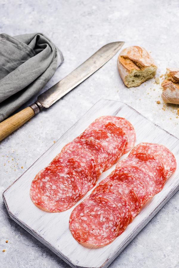 Slices of italian salami on a wooden small cutting board on delicate background. Slices of italian salami on small cutting board on delicate background stock photography
