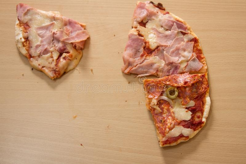 Slices of Italian stuffed pizza on a wooden table that disappear one by one royalty free stock photography