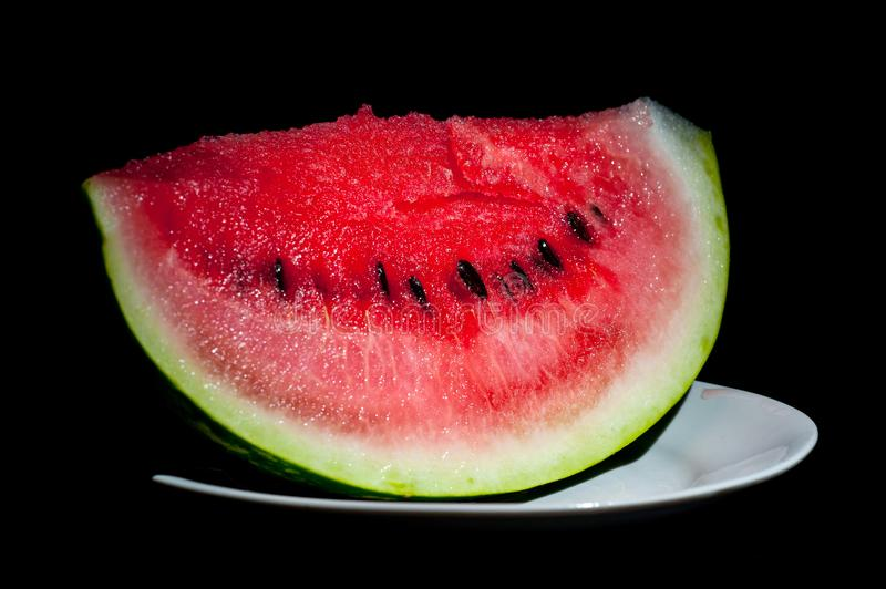 Slices of juicy watermelon shot close-up on a dark background royalty free stock image
