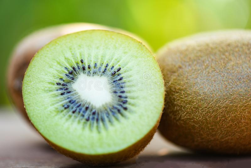 Slices kiwi close up and fresh whole kiwi fruit wooden and nature green background. Slices kiwi close up and fresh whole kiwi fruit on wooden and nature green royalty free stock photo