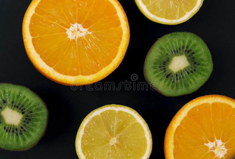 Slices of kiwi, lemon and orange on a black background, on a chalk board. There is a place for text stock photos