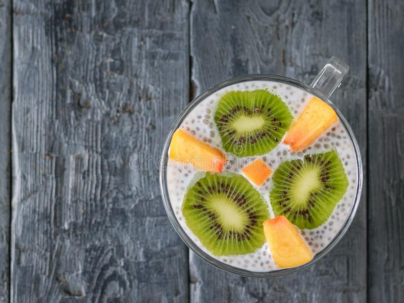 The slices of kiwi and peach in the pudding of the Chia seeds with the milk. The view from the top royalty free stock photo