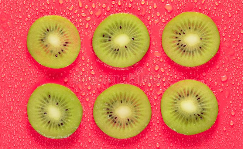 Slices of kiwi in water drops on a red background. Fruit concept. stock photography