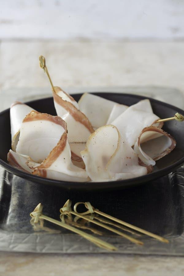 Slices of Lardo di colonnata for aperitif royalty free stock images