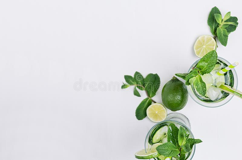 Slices lime, cucumber, leaves mint, ice and transparent cold drink on white wood plank, top view, copy space. royalty free stock photo