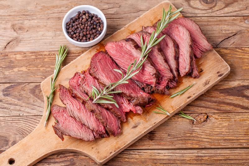 Slices of medium rare roast beef meat on wooden cutting board. Top view. stock images