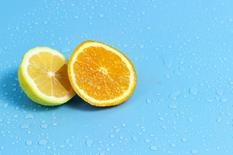 Slices of orange and lemon on a blue background with water drops. Summer cool water orange slices stock photo