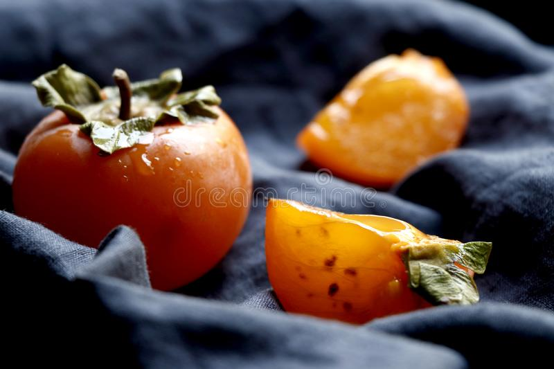 Slices of Orange red persimmon fruit.Fresh kaki on classical blue cloth. Set of persimmons royalty free stock photos