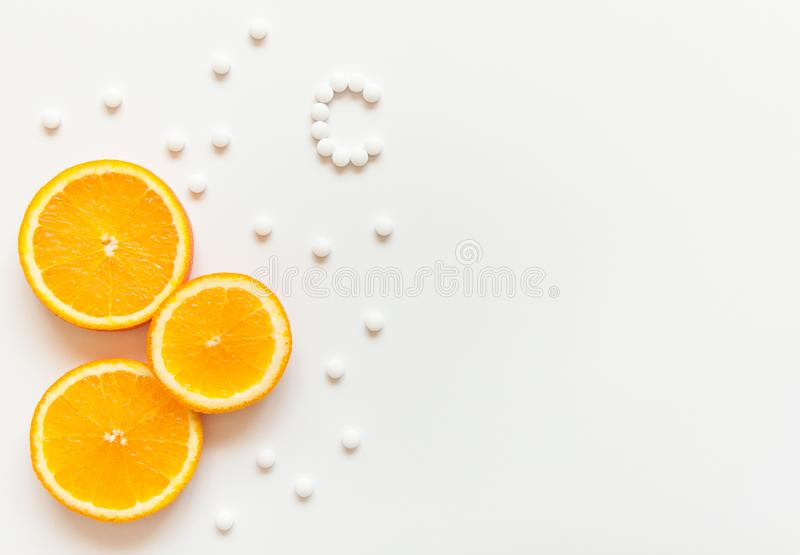 Slices of orange on a white background. Fruit with vitamins. Tablets with vitamin C against colds. Exotic tropical fruit for juice. Orange food. Meals for royalty free stock photo