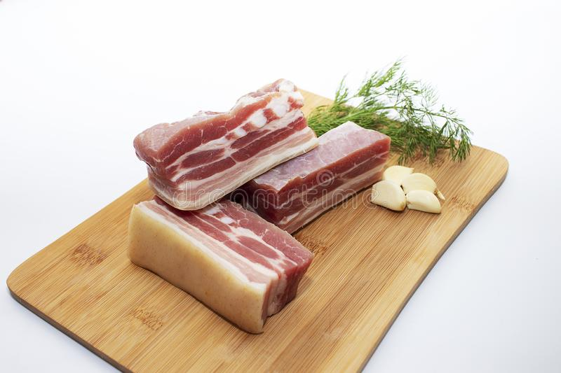 Slices of pork belly with garlic and herbs on a cutting board. Juicy slices of meat with bacon with pepper stock images