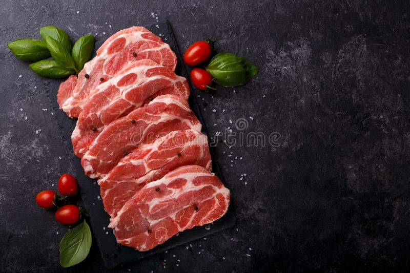 Slices pork loin. With herbs salt and pepper black stone background copy space flat lay stock photography