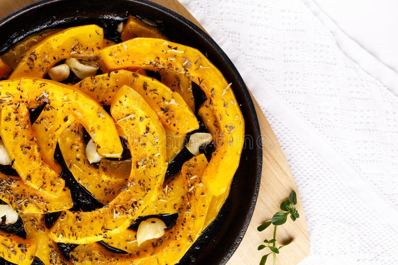Slices of pumpkin baked with garlic and herbs royalty free stock photo