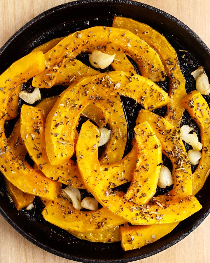 Slices of pumpkin baked with garlic and herbs stock images
