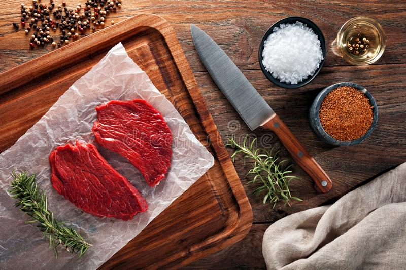 Slices of raw calf beefsteak on white cooking paper and wooden cutting table royalty free stock images