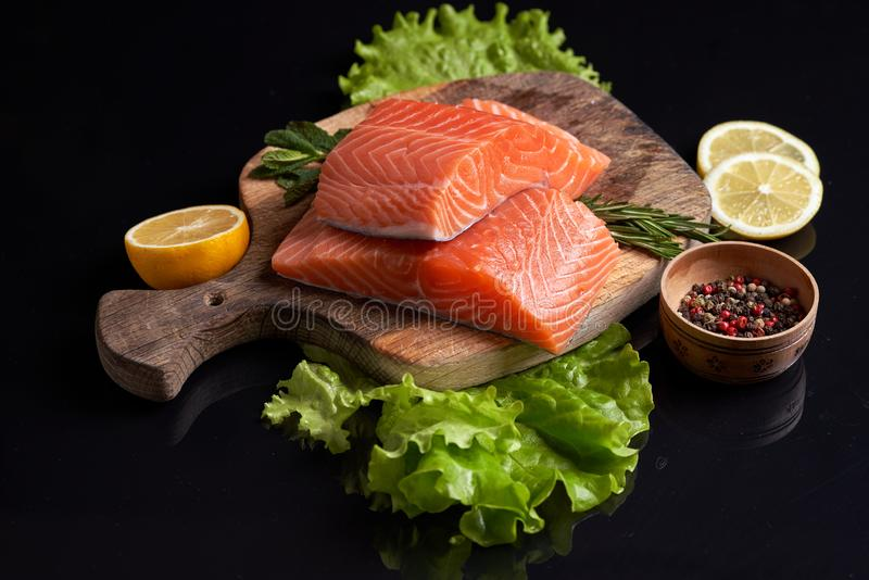 Slices of raw red fish fillet on a cutting board with lettuce, lemon slices, rosemary, colorful peppercorns royalty free stock images