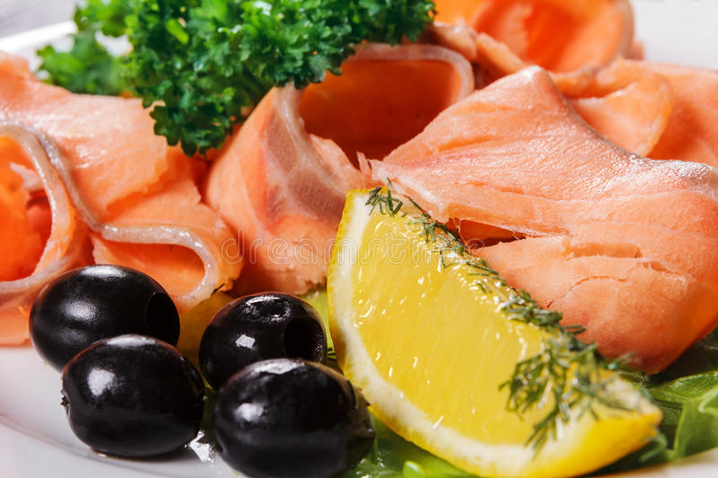 Slices of red fish with lemon and olives on plate royalty free stock image