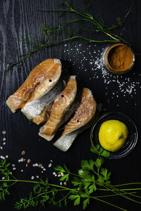 raw salmon on trout steak with spices, pepper, lemon, parsley, dill, salt, selery greens on black wooden background with copy spac stock photo