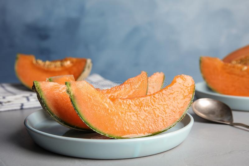 Slices of ripe cantaloupe melon in plate on grey royalty free stock image