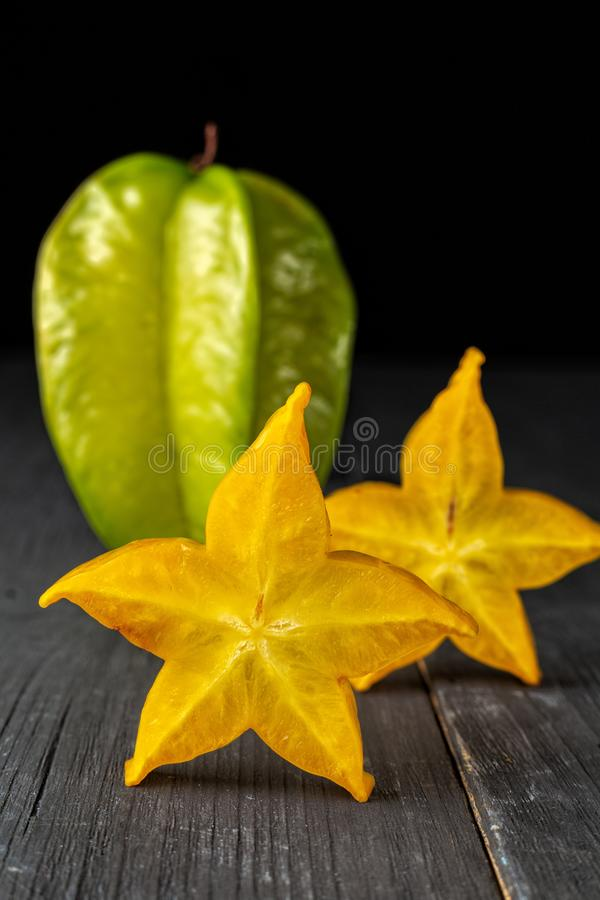 Slices of ripe star fruit carambola or star apple starfruit , and whole fruit on dark background, vertical composition stock image