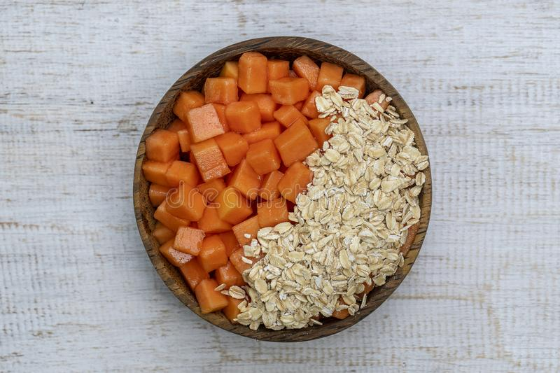 Slices of sweet papaya with oat flakes in coconut bowl on white wooden background, close up. Slices of ripe sweet papaya fruit with oat flakes on coconut bowl on stock photo