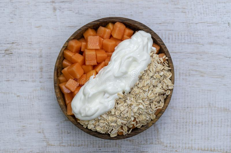 Slices of sweet papaya with oat flakes and white yogurt in coconut bowl on white wooden background, close up. Slices of ripe sweet papaya fruit with oat flakes stock photography