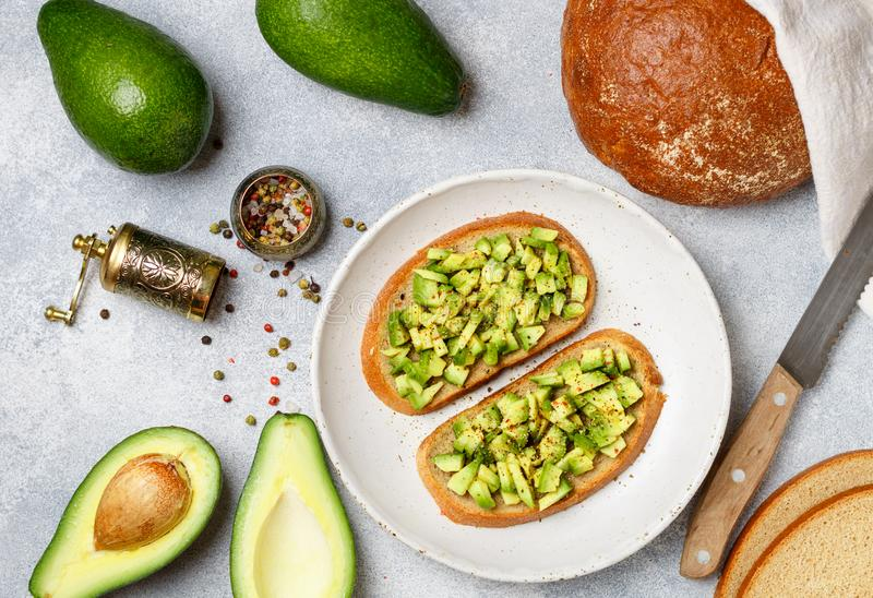 Slices of rye bread with avocado and spices. Colorful peppers and large sea salt, black sesame. Guacamole. Sandwiches and ingredients on the table. Selective royalty free stock images