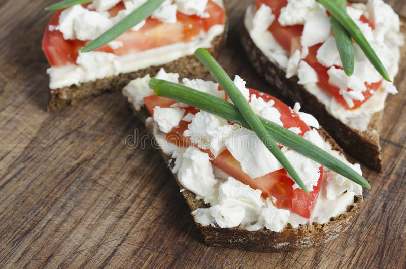 Slices of rye bread with sire feta, tomato and onion. Slices of rye bread with sire feta, tomato and onion on a wooden board. Selective focus royalty free stock image