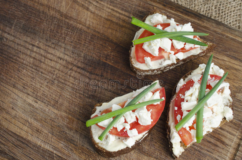 Slices of rye bread with sire feta, tomato and onion. Slices of rye bread with sire feta, tomato and onion on a wooden board. Selective focus royalty free stock photography