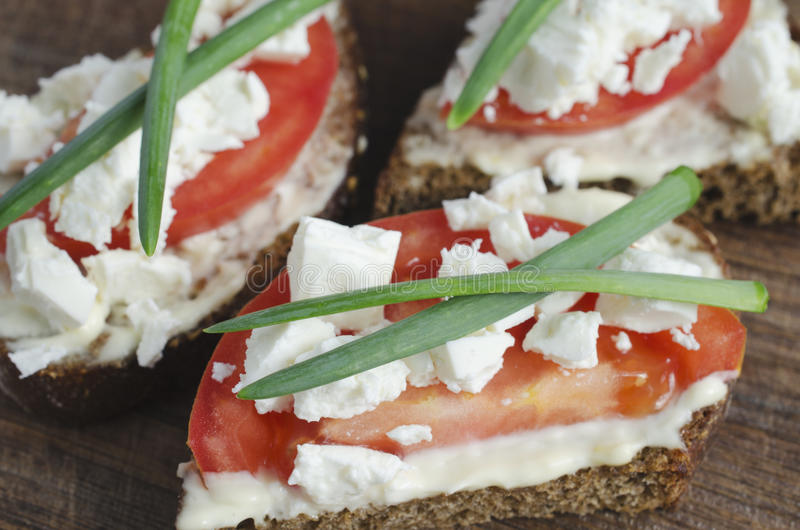 Slices of rye bread with sire feta, tomato and onion. Slices of rye bread with sire feta, tomato and onion on a wooden board. Selective focus stock images