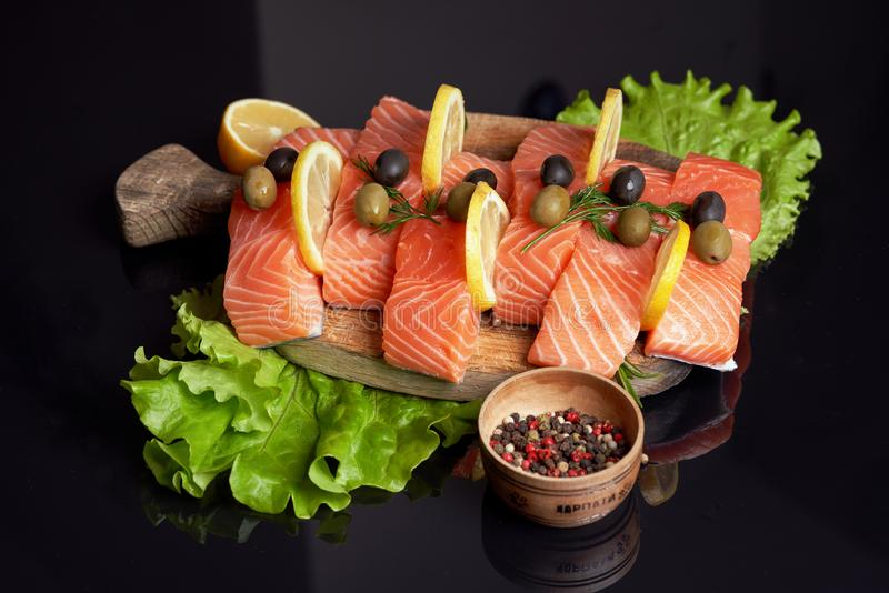 Slices of salmon fillet on a cutting wooden board with lemon slices, lettuce, green and black olives, colorful peas. Cooking fish stock images