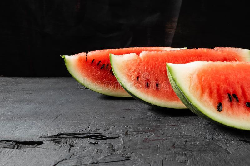 Slices and slice of watermelon in black background stock images