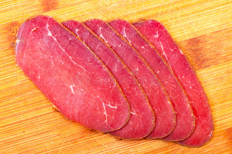 Slices of Smoked Meat. On wood background stock photos