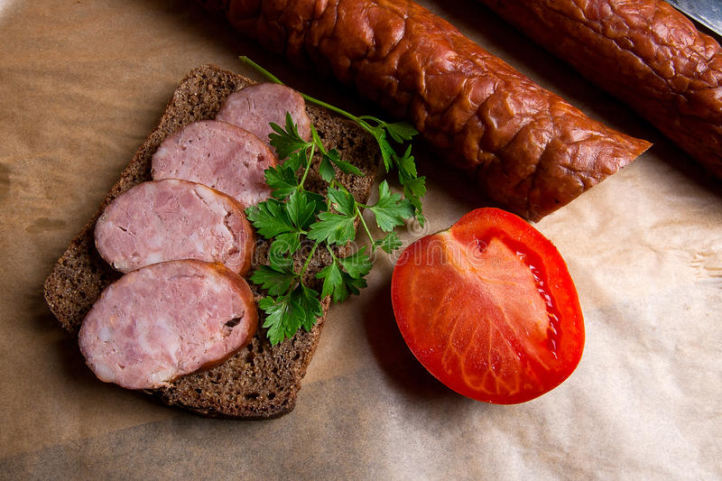 Slices of smoked sausage with spice, herbs and vegetables on the. Close up view slices of smoked sausage with parsley and rye black bread, several tomatoes and stock photo