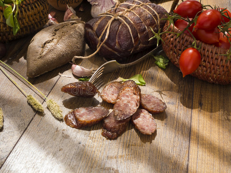 Slices of smoked sausages with bacon, bread, tomatos, herbs, garlic on wooden board. Slices of smoked sausages with bacon, bread, tomatos, garlic on wooden board stock images