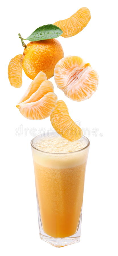 Slices of tangerine falling into a glass of fresh stock images