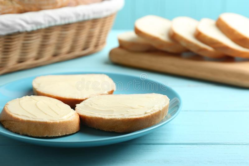 Slices of tasty fresh bread with butter on blue wooden table. Slices of tasty fresh bread with butter on light blue wooden table stock photos
