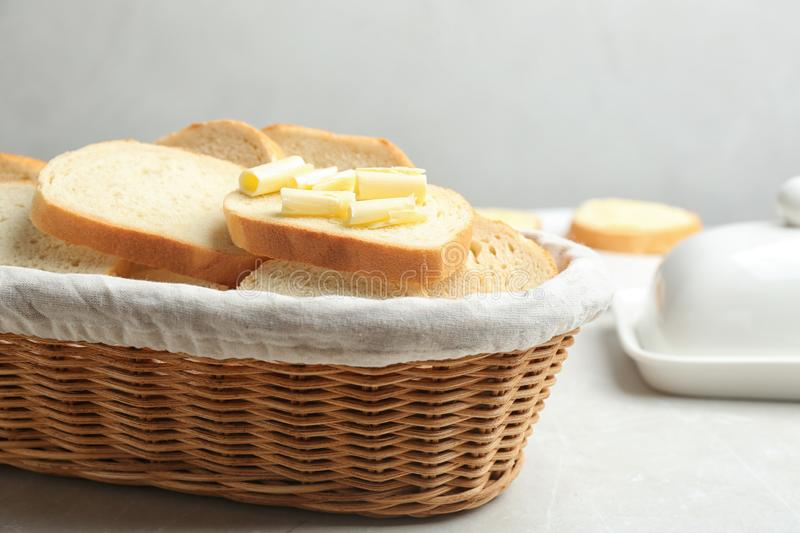 Slices of tasty fresh bread with butter in wicker basket on marble table. Slices of tasty fresh bread with butter in wicker basket on light marble table royalty free stock photos