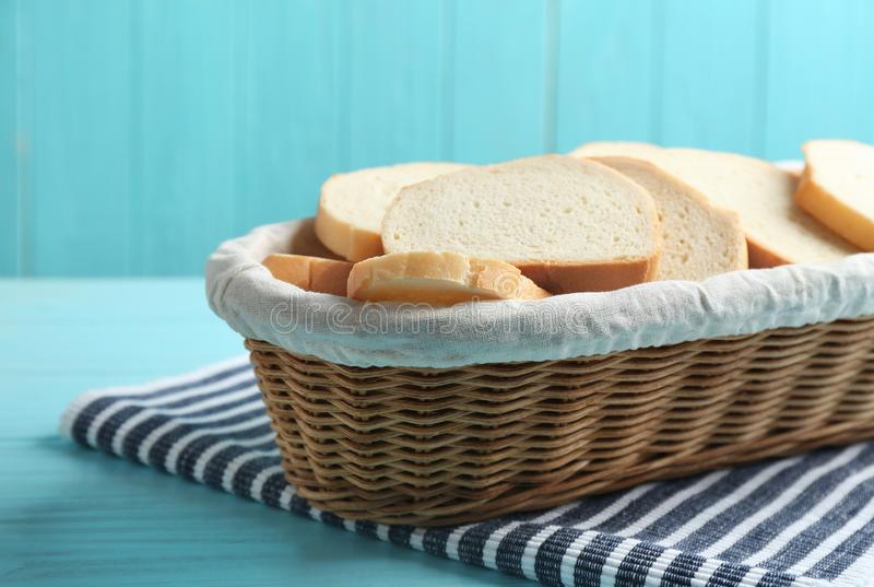 Slices of tasty fresh bread in  basket on light blue wooden table, closeup stock photo