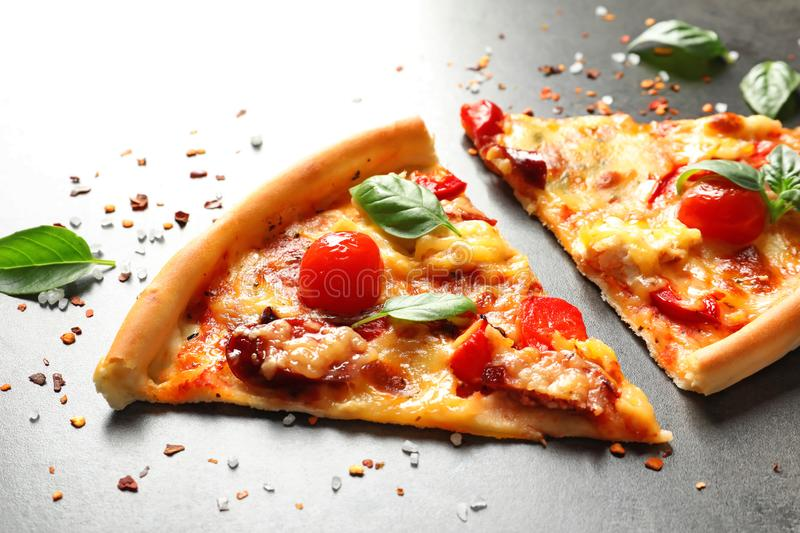 Slices of tasty pizza with tomatoes and sausage s on table royalty free stock photos