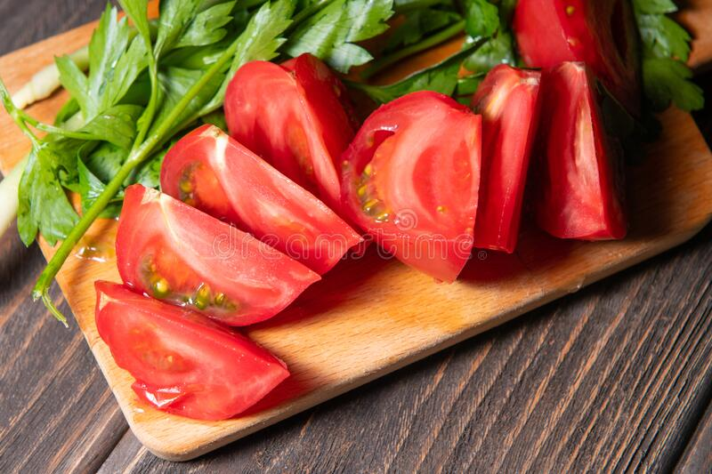 Slices tomatoes served with greenery stock image