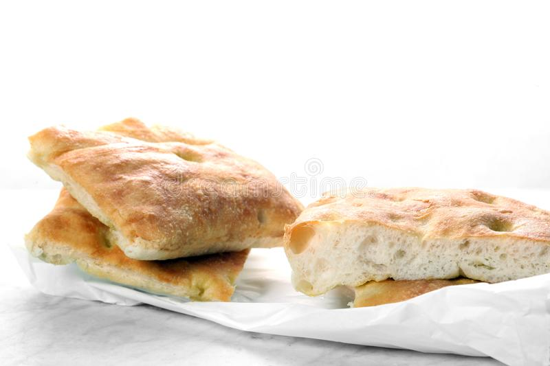 Slices of traditional italian focaccia  rest on a wooden cutting board with copy space for your text royalty free stock photo
