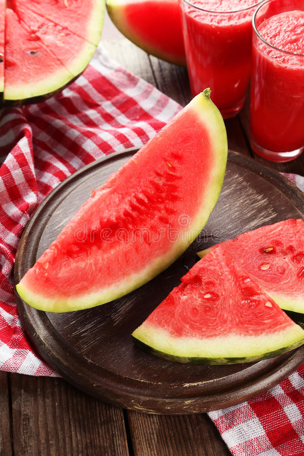 Slices of watermelon on brown wooden background stock photos
